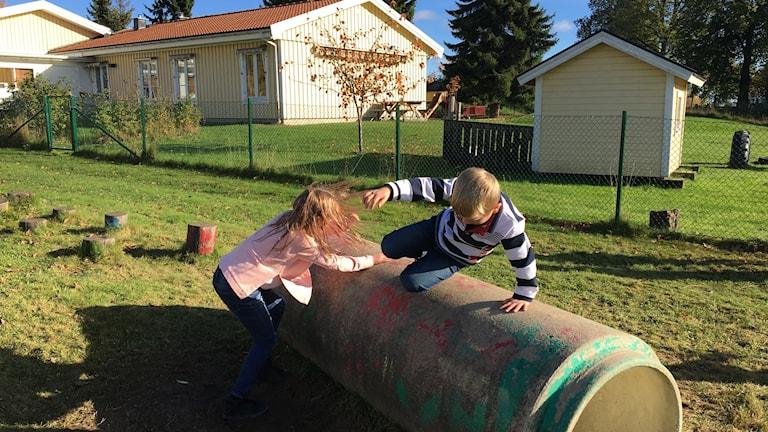 Två barn hoppar över ett rör utomhus.