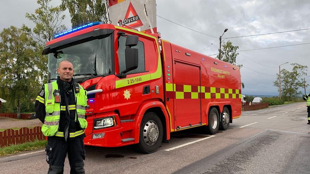 """Räddningsledare i gul väst framför stor rödgul bil med """"olycka""""-skylt på taket."""