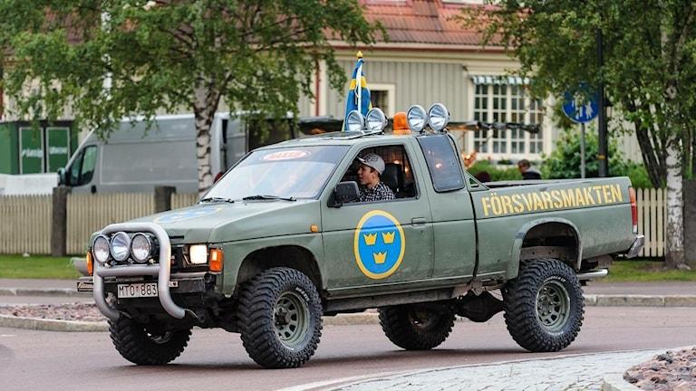 En person kör ett militärgrönt fordon med texten Försvarsmakten på.