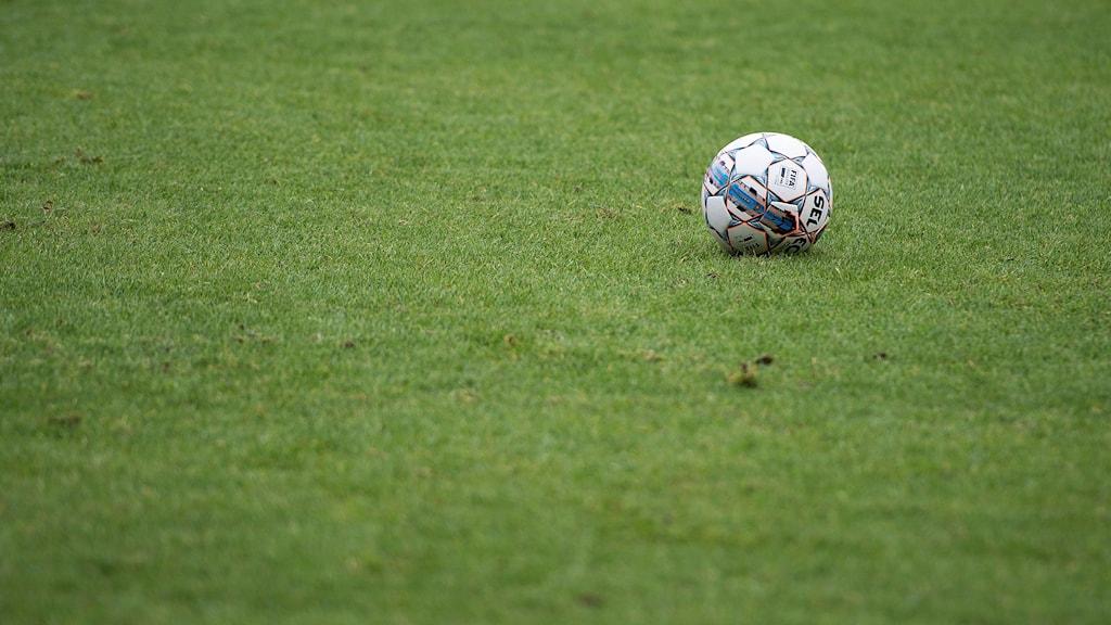 Fotboll på en grön fotbollsplan.