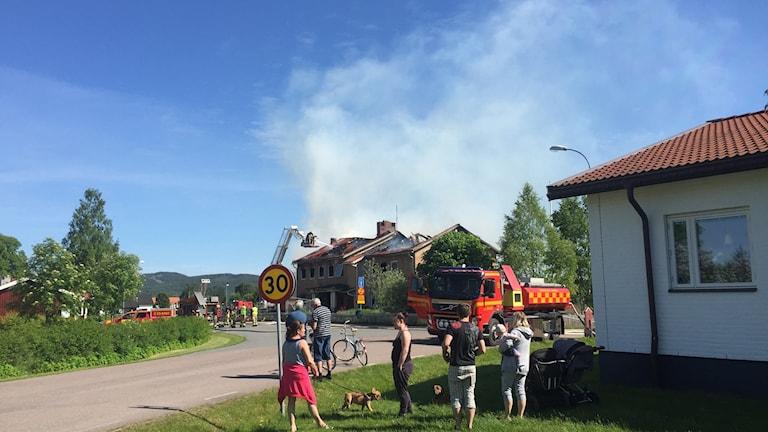 Folk står och tittar på när räddningstjänsten släcker en husbrand i Insjön.