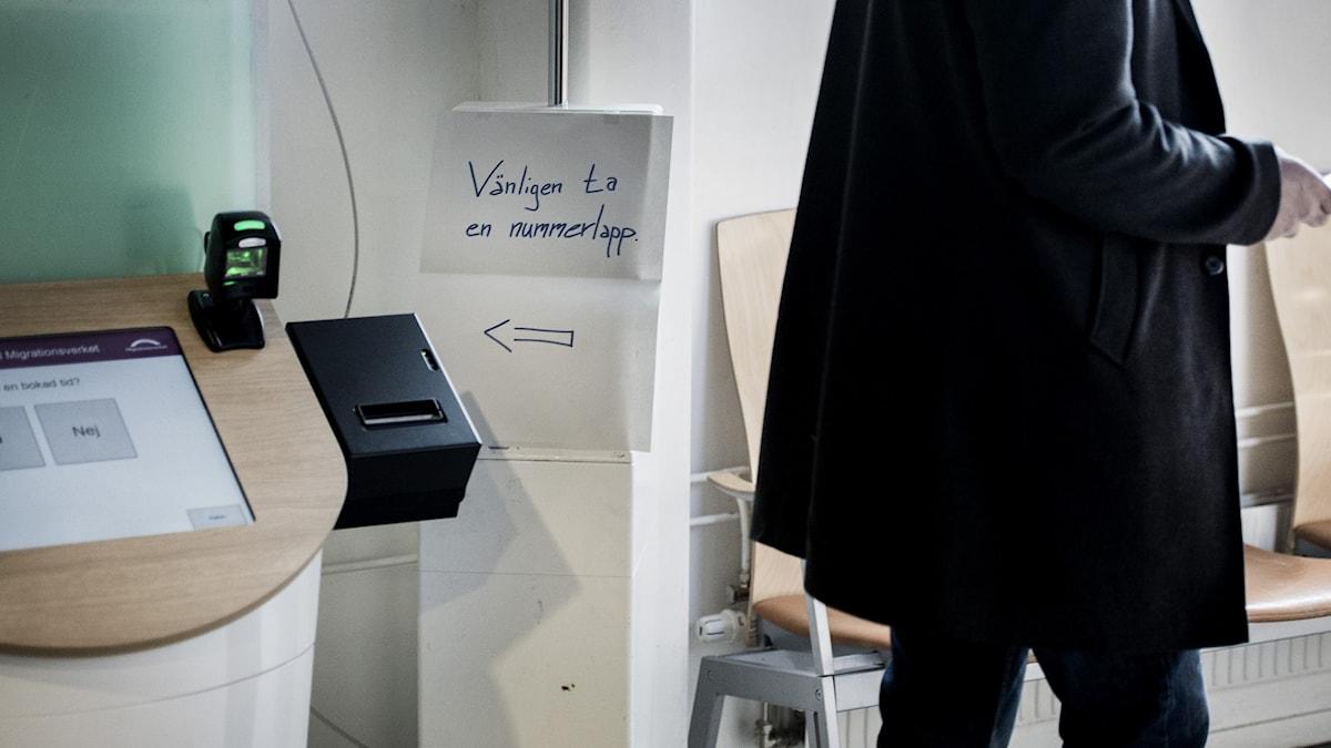 En människa bredvid en maskin med nummerlappar, på Migrationsverket.