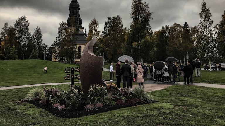 En grupp med människor står med paraplyer framför en kyrka.