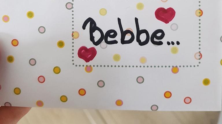 """Bild på ett kuvert med prickar, hjärtan och en text där det står """"Bebbe""""."""