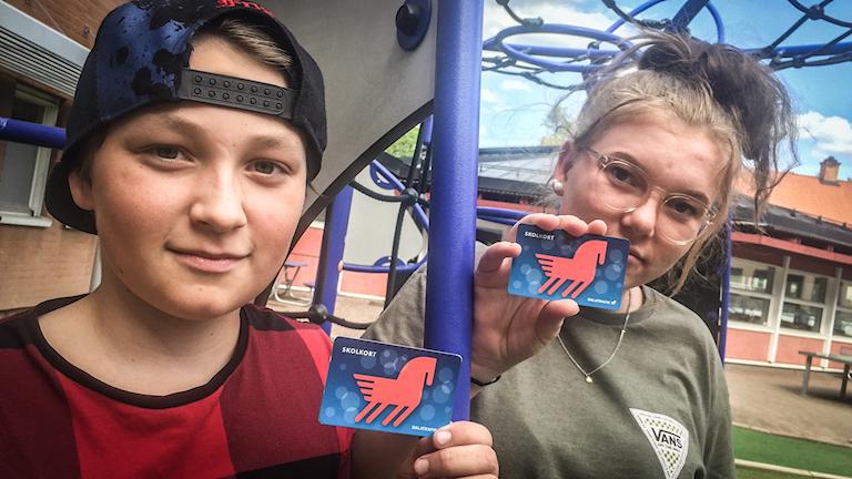 Theo Hoff och Ebba Eld håller upp sina busskort på skolgården i Falun.