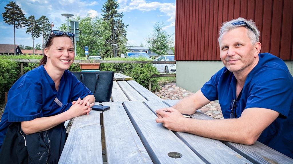 En man och en kvinna i blå kortärmade tröjor sitter vid ett träbord.