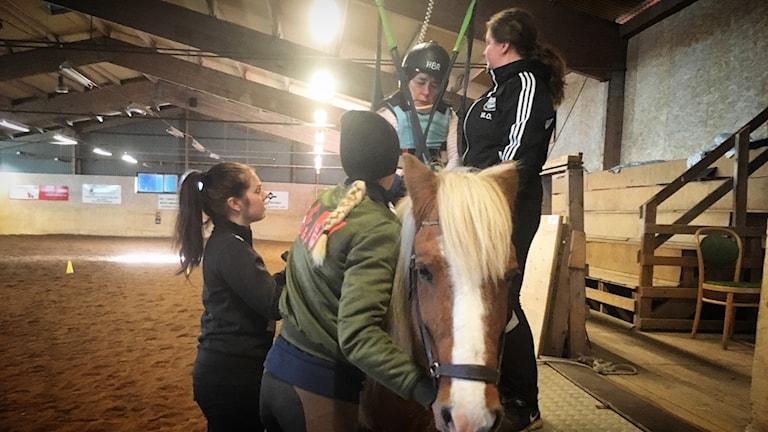 Linda får hjälp upp på hästen av flera assistenter.