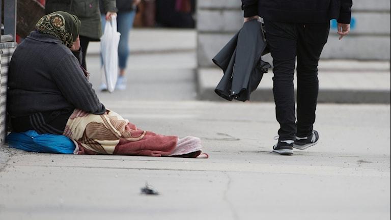 En tiggare sitter på gatan