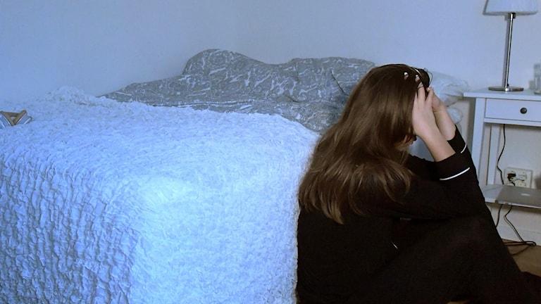 En kvinna sitter på golvet vid sin säng