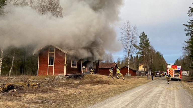 Brandmän arbetar med att släcka brand i ett falurött hus med vita knutar. Inga lågor syns men däremot mycket rök.