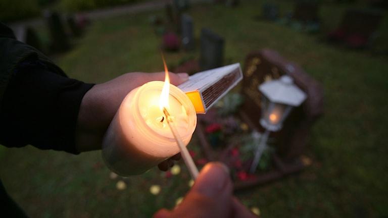 Person tänder ett gravljus, i bakgrunden syns en gravsten i skymningsljus.