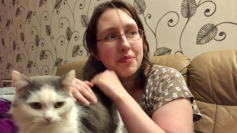 Petra Lindvall sitter i sin soffa med en av sina gråvita katter.