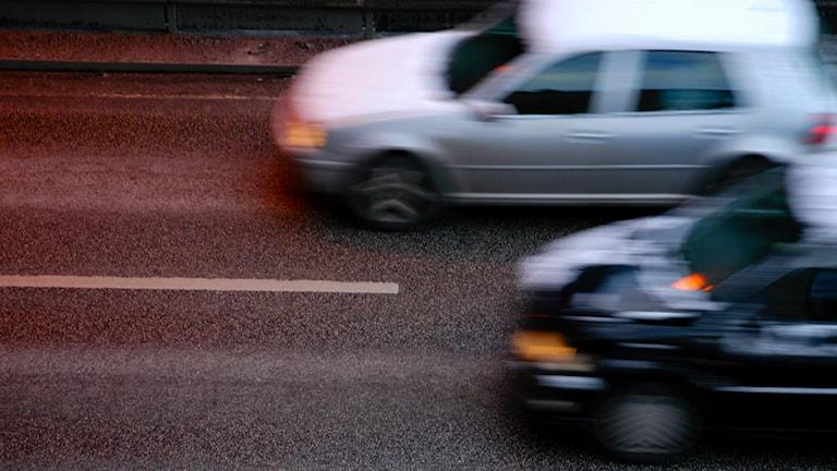 Bilar som kör på en tvåfilig väg.