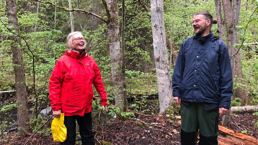 En kvinna och en man står ute i skogen.