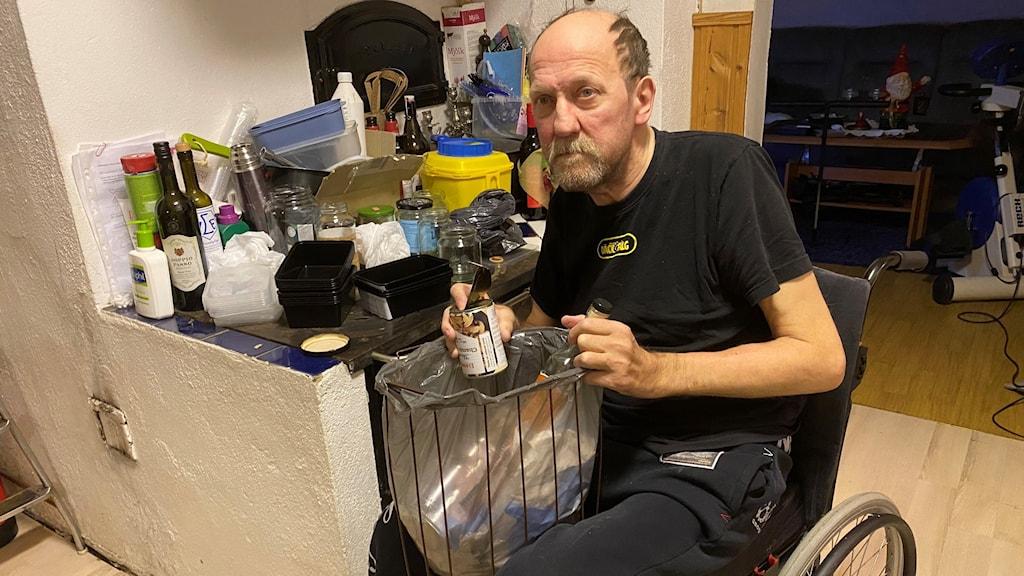 Man i rullstol sitter framför sopor som ska återvinnas som ligger på hans vedspis. I knät har han sin sopkorg där han visar att det ligger plåtburkar.