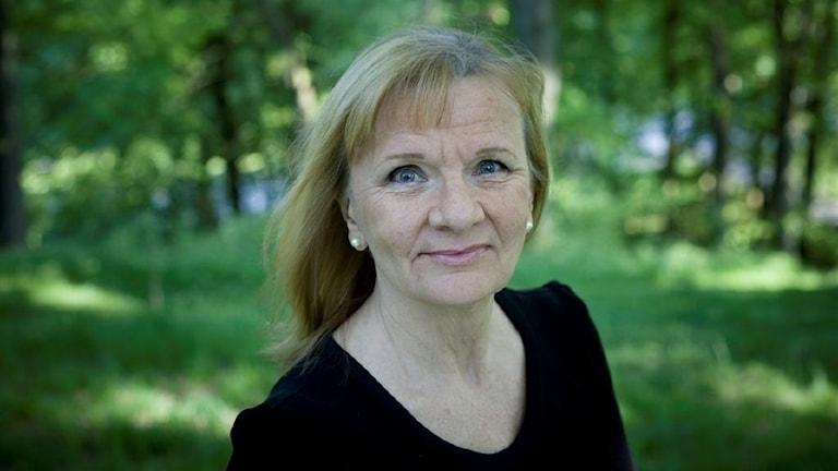 Författaren Aino Trosell i en somrig, grön skogsdunge.