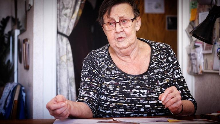 81-åriga Margareta Söderström sitter vid sitt köksbord med kontoutdrag och räkningar framför sig.