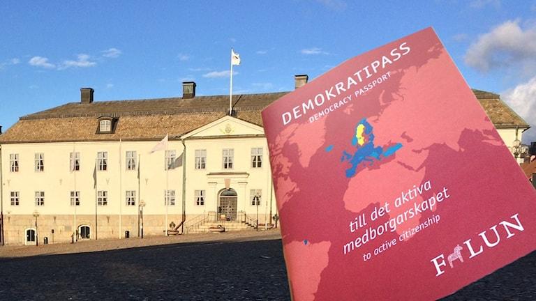 Bildkollage med demokratipass i förgrunden och rådhuset i Falun i bakgrunden.