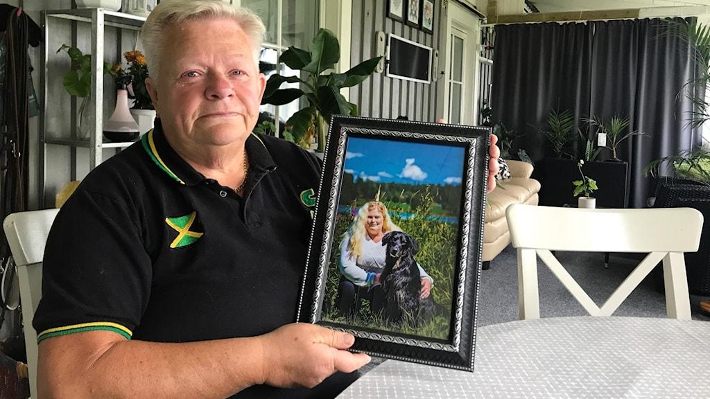 En kvinna i svart, kort hår sitter vid ett bord och håller upp en inramad bild på en kvinna med en hund.