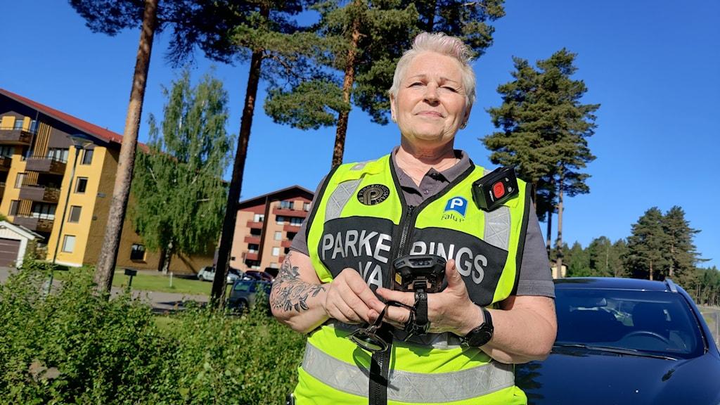 Parkeringsvakt i gul väst med röd knapp på en dosa vid axeln. Kort, blont hår med uppåtlugg, tatuering på ena armen.