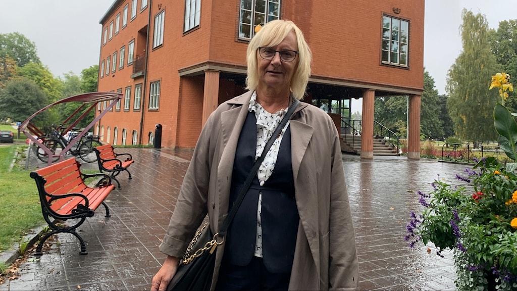 En kvinna står i kappa och axelremsväska framför Ludvikas tegelbruna kommunhus.