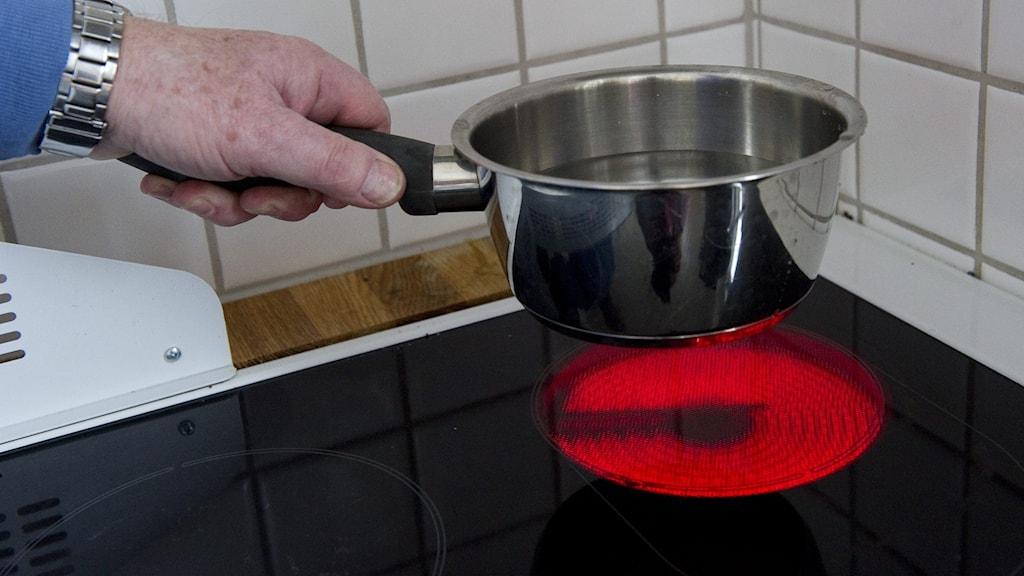 En person ställer ner en kastrull med vatten på spisen.