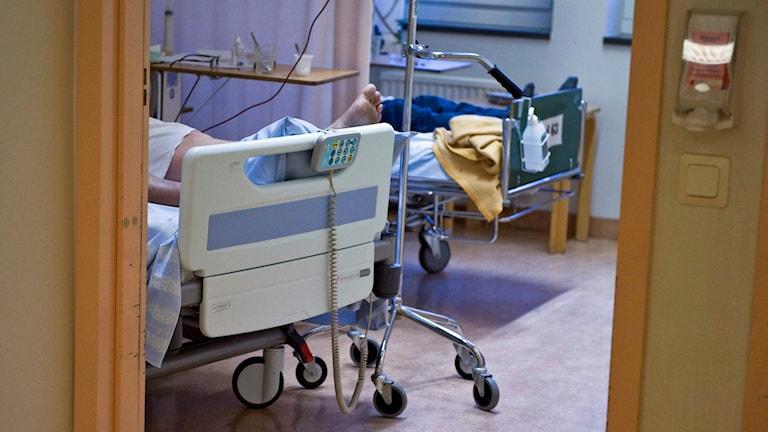 Säng på ett sjukhus med patient i - man ser en fot.