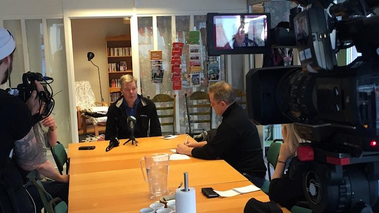 Leif Lindström sitter vid änden av ett bord med mikrofoner och tevekameror riktade mot sig.