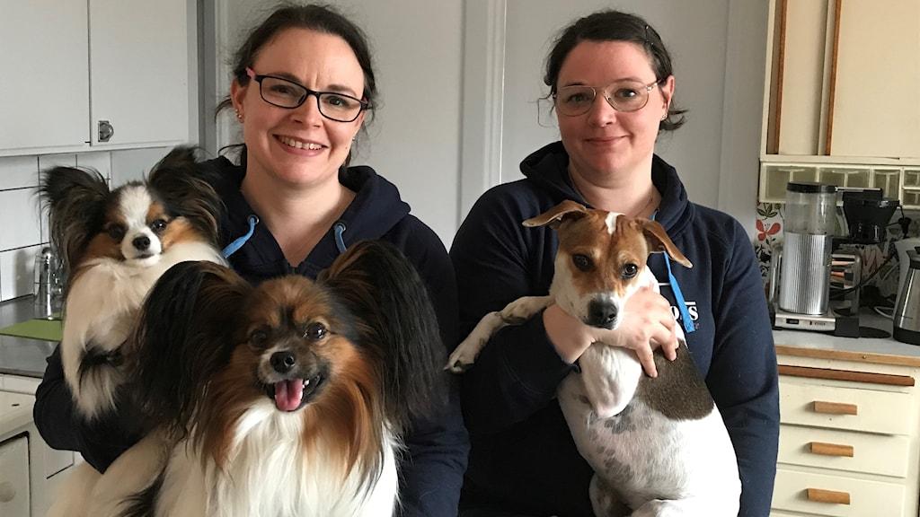 Två kvinnor med mörkt hår och svarta tröjor står bredvid varandra. Den ena håller två hundar i famnen, den andra håller en hund i famnen.