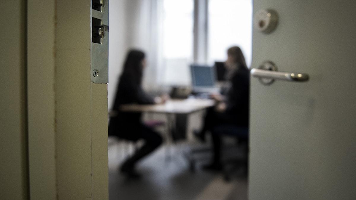 I förgrunden en dörrkarm och en dörr, suddigt inne i rummet syns två personer som sitter på varsin sida om ett skrivbord.