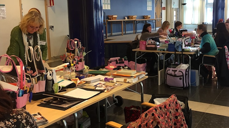 Kvinnor som står och sitter vid bord fyllda med pysselsaker.