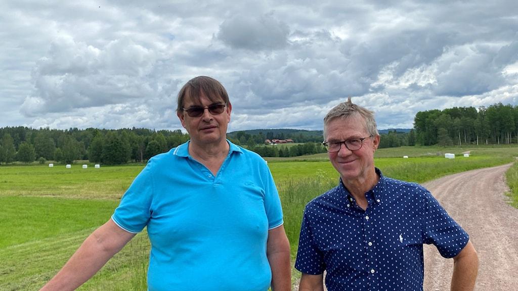 Fotot visar två män mede glasögon på en grusväg.