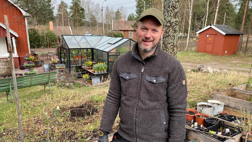 En man i mörkgrön keps ler in i kameran, i bakgrunden ser man en trädgård med växthus.