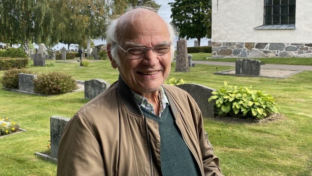 Lennart Stålberg står framför kyrkan, man ser några gravstenar i bakgrunden och lite av en vit kyrka.
