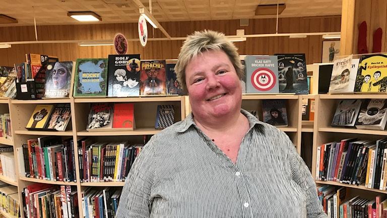 Fotot visar en kvinna som står fram en hylla med böcker i biblioteket.