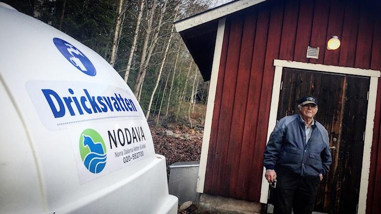 Bybon Lars-Erik Larsson står framför ett rött litet hus som är Klittens vattenverk. Han har blå jacka och keps på sig. I förgrunden syns vattenbolaget Nodavas dricksvattentank som är utplacerad temporärt medan dricksvattnet i kranen inte går att dricka.