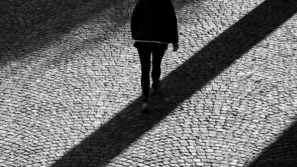 Person går över kullerstenar med solljus som kastar långa skuggor.