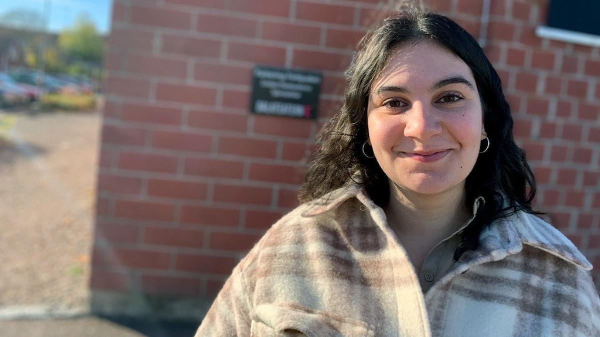 Lina Leandersson, en kvinna med mörkt hår och rutig jacka står framför Dalateaterns tegelvägg.