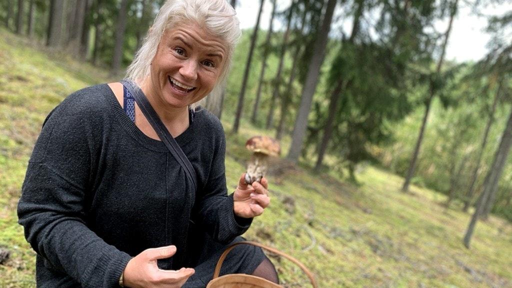 Utekocken och svampkännaren Elle Nikishkova sitter i en skog vid en korg och håller upp en svamp.