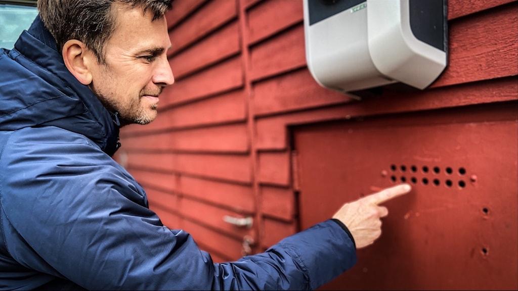En man sitter vid ett rött trähus och pekar på en liten röd metalldörr med ventilationshål i.