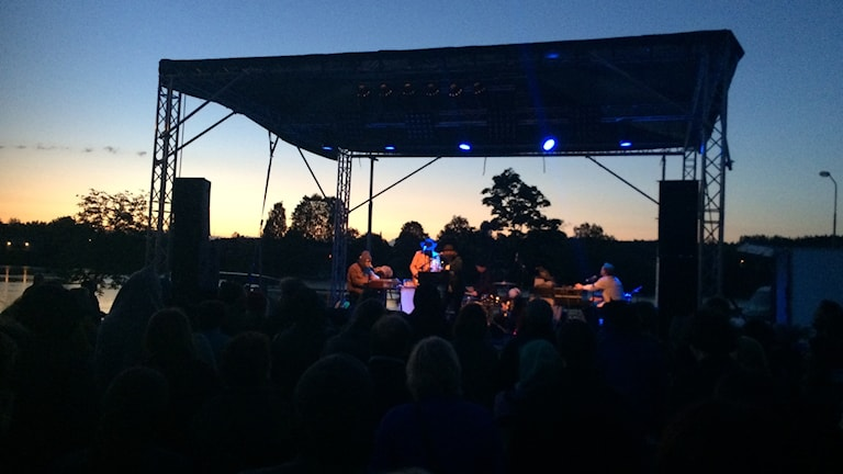 En scen med ett band på i solnedgång.