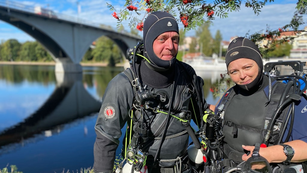 Två personer i dykutrustning som står framför en älv.