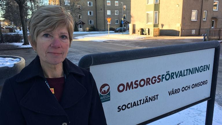 """Carina Johansson står framför omsorgshuset i Avesta bredvid en skylt där det står """"omsorgsförvaltningen""""."""