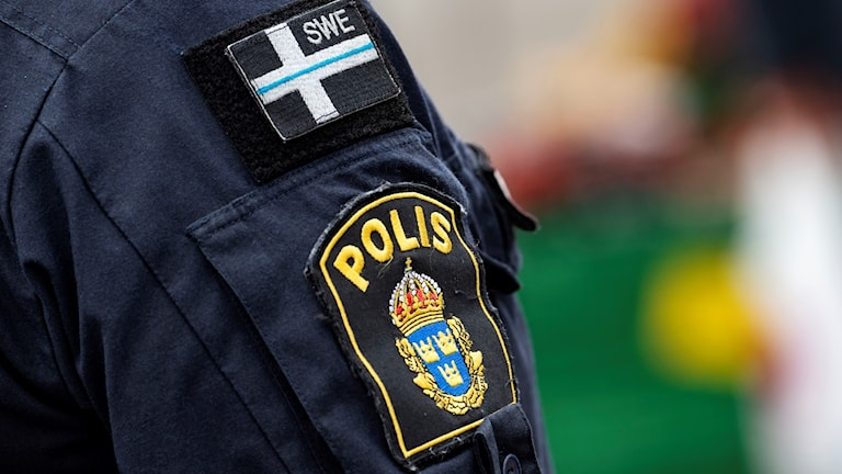 På fotot syns en axel av en polis, med polisuniform.
