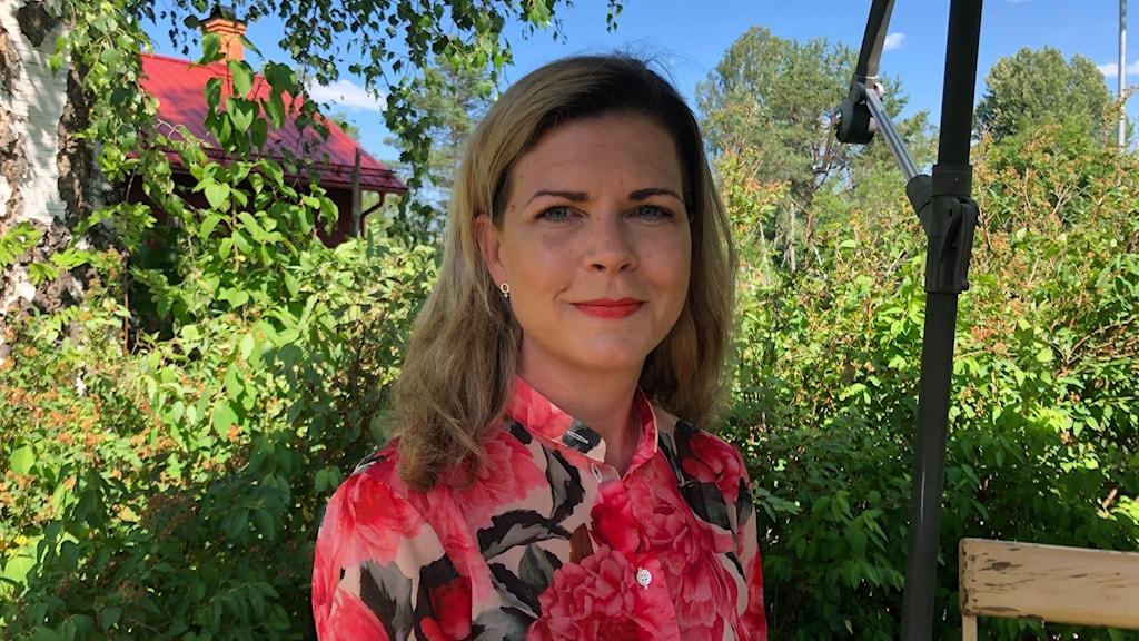 Sofia Jarl (C) i en trädgård.