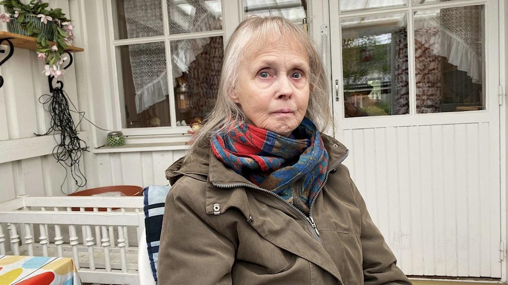 Kvinna i tjock jacka sitter på veranda.