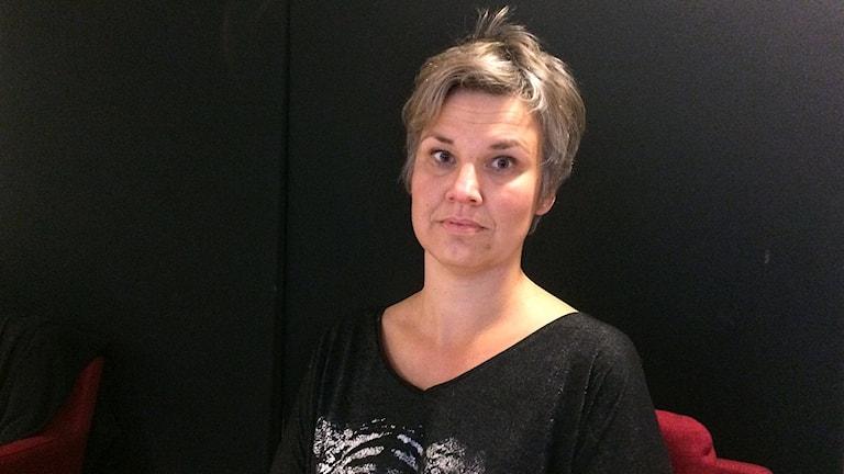 Karin Svens med allvarlig min mot svart bakgrund.