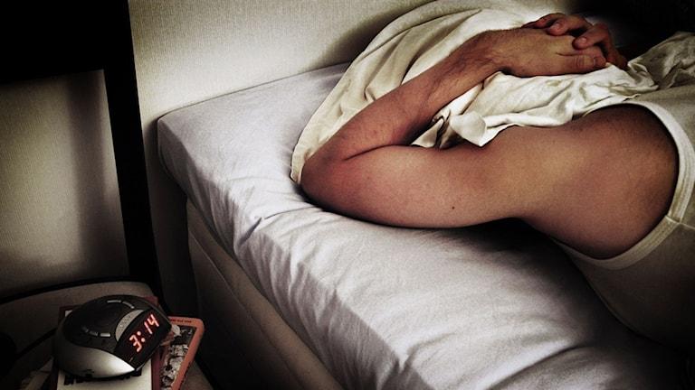 En man som ligger i en säng med kudde över huvudet.