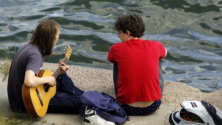 Två tonårspjkar som sitter på klipporna vid en sjö.