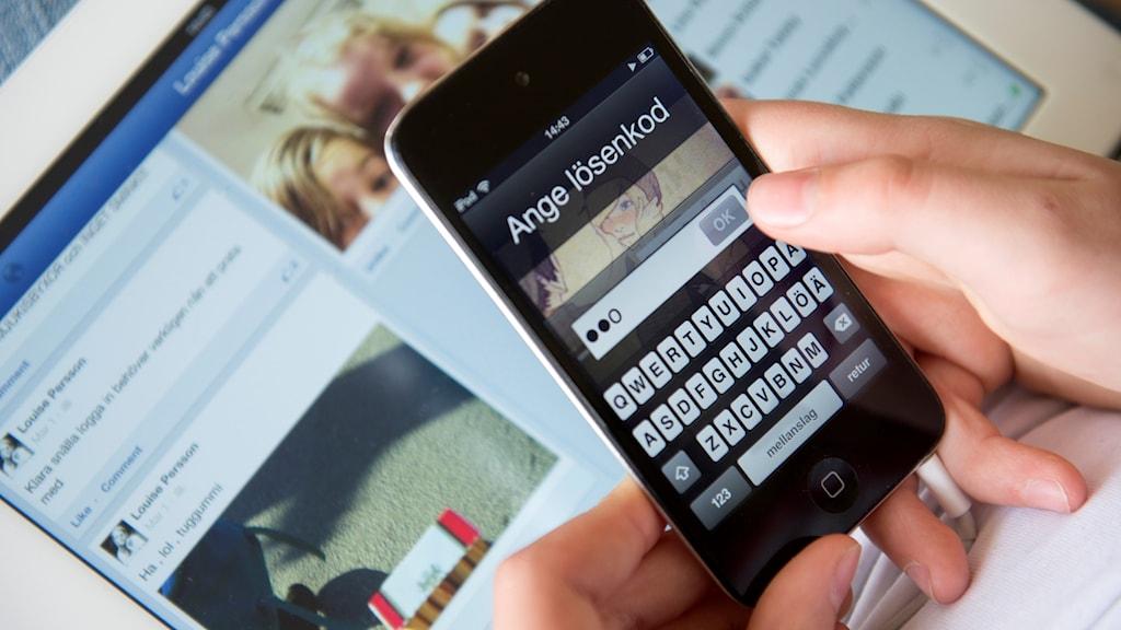 Händer håller i en mobiltelefon som frågar efter lösenkod, i bakgrunden syns en datorskärm med Facebook uppe.